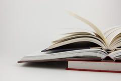 Zwei geöffnete Bücher auf einem geschlossenen Buch Lizenzfreies Stockfoto
