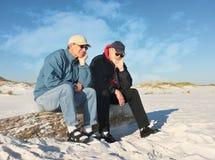 Zwei gebohrte pensionierte Männer gesetzt am Strand Lizenzfreie Stockfotos