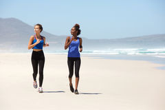 Zwei geeignete Frauen der Junge, die auf Strand laufen Stockfotos