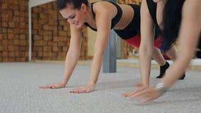 Zwei geeignete Frauen, welche die Übungen liegen innerhalb des Eignungsstudios tun stock video