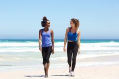 Zwei geeignete junge Frauen, die auf Strand gehen stockfotos