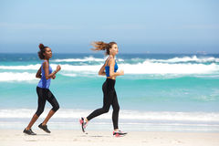 Zwei geeignete junge Frauen, die entlang den Strand laufen Lizenzfreie Stockbilder