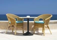 Zwei geflochtene Stühle auf dem Hintergrund des Meeres Stockbilder