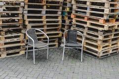 Zwei geflochtene Stühle gesetzt vor Stapeln Paletten stockbilder