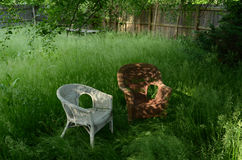 Zwei geflochtene Stühle unter Schattenbaum Stockfotografie
