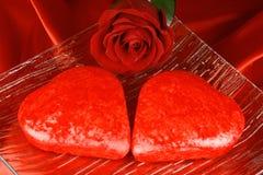 Zwei geformte Kuchen des Rotes Inneres und eine Rose Stockfotografie