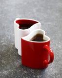 Zwei geformte Schalen des Herzens mit Tee Stockfotos