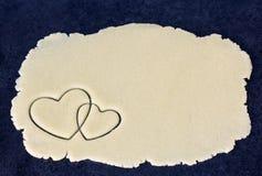 Zwei gekreuzte Herzen auf Teigschicht Stockfotografie
