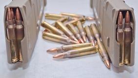 Zwei geladen 223 Gewehrzeitschriften mit den Kugeln, die um sie legen Stockfotografie