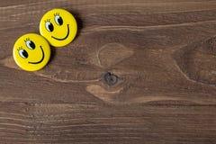 Zwei gelbe Knöpfe mit smileygesichtern auf einem hölzernen Hintergrund Stockbild