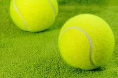 Zwei gelbe Tennisbälle auf grüner Oberfläche Lizenzfreie Stockfotos