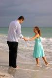 Zwei Geliebte, die Hände anhalten und am Strand sprechen Stockfotos