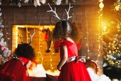 Zwei gelockte kleine Mädchen, die den Weihnachtskamin nahe b betrachten lizenzfreie stockfotos