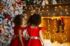 Zwei gelockte kleine Mädchen, die den Weihnachtskamin nahe schönem Weihnachtsbaum betrachten Zwillinge in den roten Kleidern, die stockbild