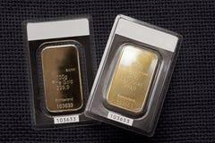 Zwei geprägte Goldbarren gegen eine dunkle Gewebebeschaffenheit Lizenzfreie Stockfotos