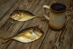 Zwei geräucherte Fische und Bierkrug auf einem Holztisch Stockbilder