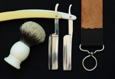 Zwei gerade Rasiermesser, Bürste und Streichriemen auf schwarzem Hintergrund Stockbilder