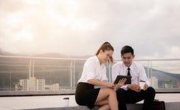 Zwei Geschäftsleute, die auf Dachboden sitzen und zusammen digitale Tablette im äußeren Geschäftslokal verwenden lizenzfreie stockfotos