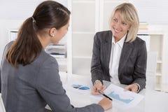 Zwei Geschäftsfrau, die am Schreibtisch sitzt: Kunden- und Beraterunterhaltung lizenzfreies stockbild