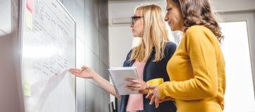 Zwei Geschäftsfrau, die vor dem whiteboard sich bespricht Lizenzfreies Stockbild