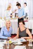 Zwei Geschäftsfrauen arbeiten während des Lebesmittelanschaffungbuffets Lizenzfreies Stockbild