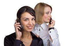 Zwei Geschäftsfrauen, die auf Handy sprechen Stockfotografie