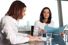 Zwei Geschäftsfrauen, die Dokumente überprüfen stockbild