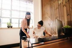 Zwei Geschäftsfrauen, die Dokumente auf Schreibtisch lesen stockbilder