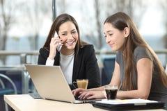Zwei Geschäftsfrauen, die in einer Stange zusammenarbeiten lizenzfreies stockfoto