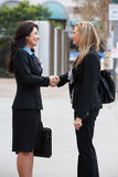 Zwei Geschäftsfrauen, die Hände außerhalb des Büros rütteln Lizenzfreies Stockbild