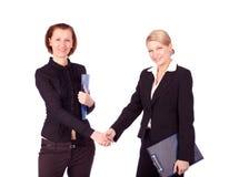 Zwei Geschäftsfrauen, die Hände rütteln Stockfotos