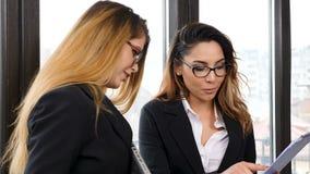 Zwei Geschäftsfrauen, die nahe dem Fenster sprechen stock video footage