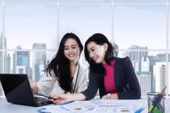 Zwei Geschäftsfrauen, die an Schreibtisch arbeiten Stockbilder