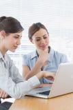 Zwei Geschäftsfrauen, die zusammen an Laptop arbeiten Stockfotografie