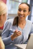 Zwei Geschäftsfrauen im Sitzungssaal mit der Laptopunterhaltung Lizenzfreie Stockbilder