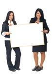 Zwei Geschäftsfrauen mit unbelegtem Schild Lizenzfreie Stockfotografie