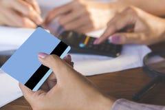 Zwei Geschäftsfrauhand, die auf Taschenrechner zählt und Kreditkarte, Schuldeneintreibung und online kaufen hält Lizenzfreies Stockbild