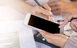 Zwei Geschäftsfrauhandschrift und mit Handy für ihre Arbeit, die auf Finanzprojekt mit Geschäftsdiagramm analysiert Stockbild
