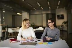 Zwei Geschäftskollegen lösen ihre Jobaufgaben mit Notizbüchern und moderne Technologie in der Universität Stockfotos