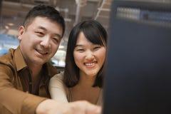 Zwei Geschäftsleute, die Computer im Büro betrachten lizenzfreies stockfoto