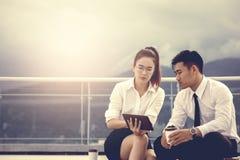 Zwei Geschäftsleute, die an der Fremdfirma sitzen und auf ta schauen stockfotografie