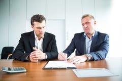 Zwei Geschäftsleute, die ein Dokument unterzeichnen stockbilder