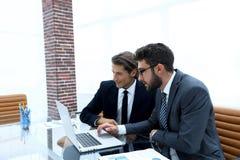 Zwei Geschäftsleute, die an einem Laptop arbeiten Lizenzfreies Stockbild