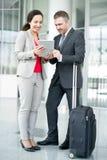 Zwei Geschäftsleute, die in Flughafen warten stockbilder