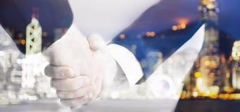 Zwei Geschäftsleute, die Hände auf undeutlichem Hintergrund rütteln Stockfotos