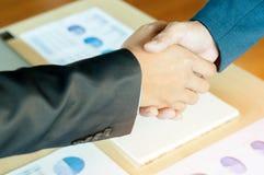 Zwei Geschäftsleute, die Hände mit Dokumentenhintergrund rütteln Stockfoto