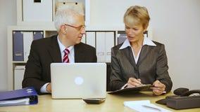 Zwei Geschäftsleute, die im Büro sprechen stock footage
