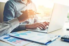Zwei Geschäftsleute, die zusammen an Laptopsitzung mit Technologie arbeiten Stockfoto