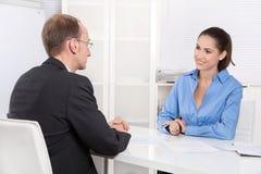 Zwei Geschäftsleute, die zusammen am Schreibtisch - Berater und custo sprechen lizenzfreies stockbild