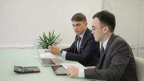 Zwei Geschäftsleute Geistesblitz vor Monitor am Schreibtisch stock video footage
